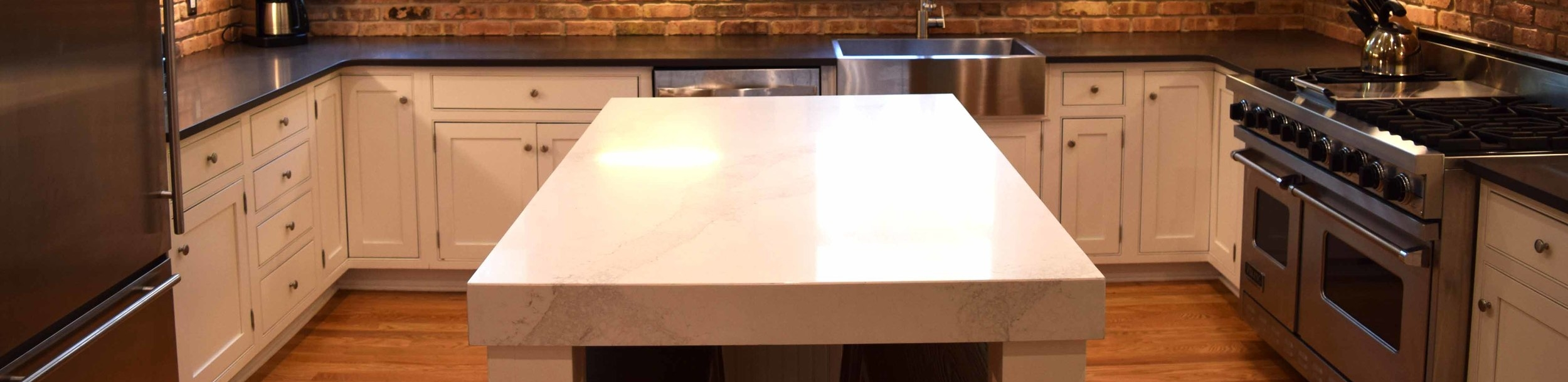 Engineered quartz countertops featured on the island above in a white marble pattern and on the surrounding countertops in black.