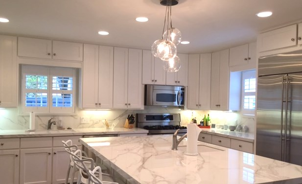 Updated bright and white kitchen featuring neolith countertops and backsplash.