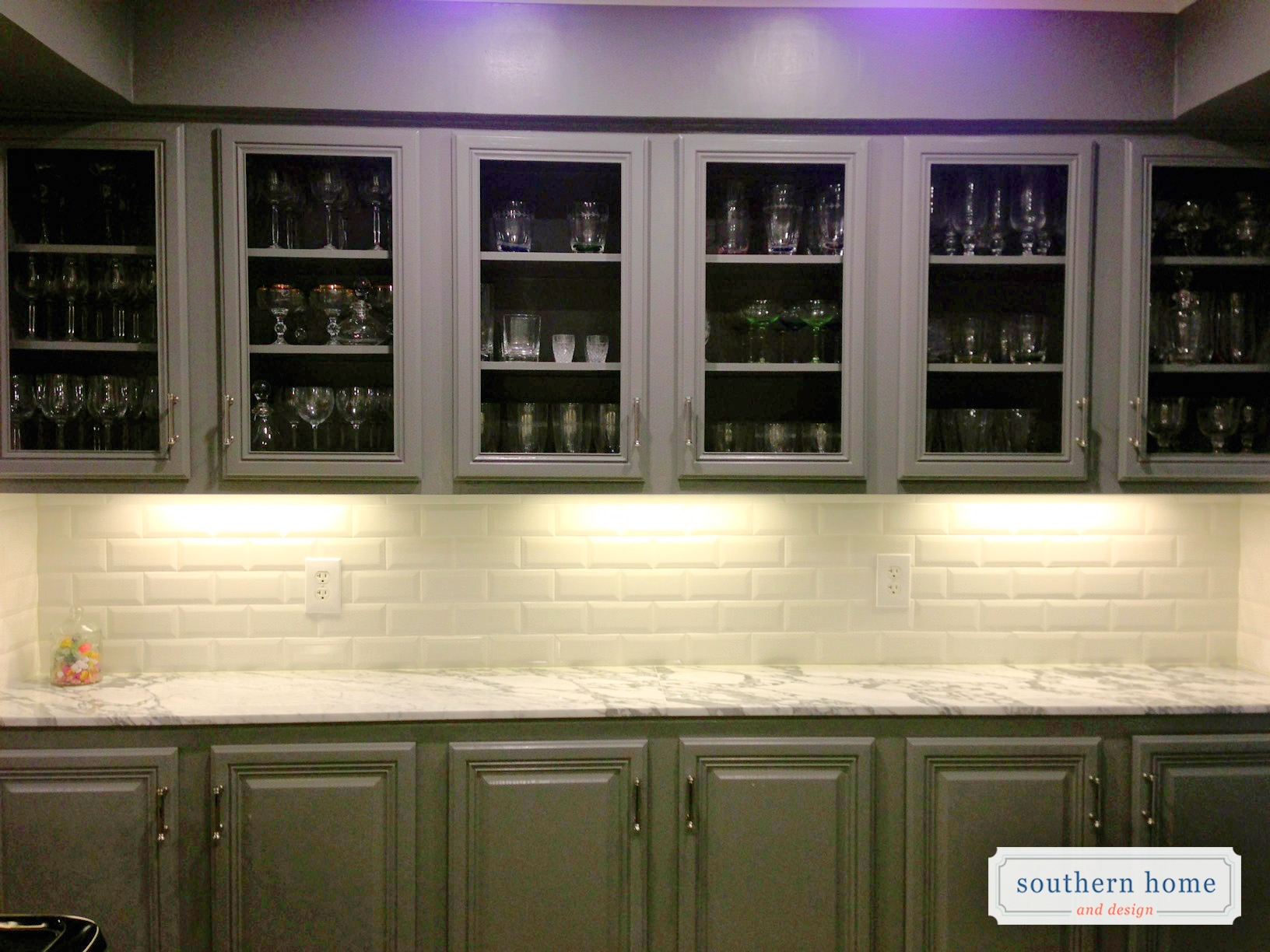 Uptown kitchen with gray raised panel and glass cabinet fronts. Carrara marble tops and white subway beveled tile backsplash.
