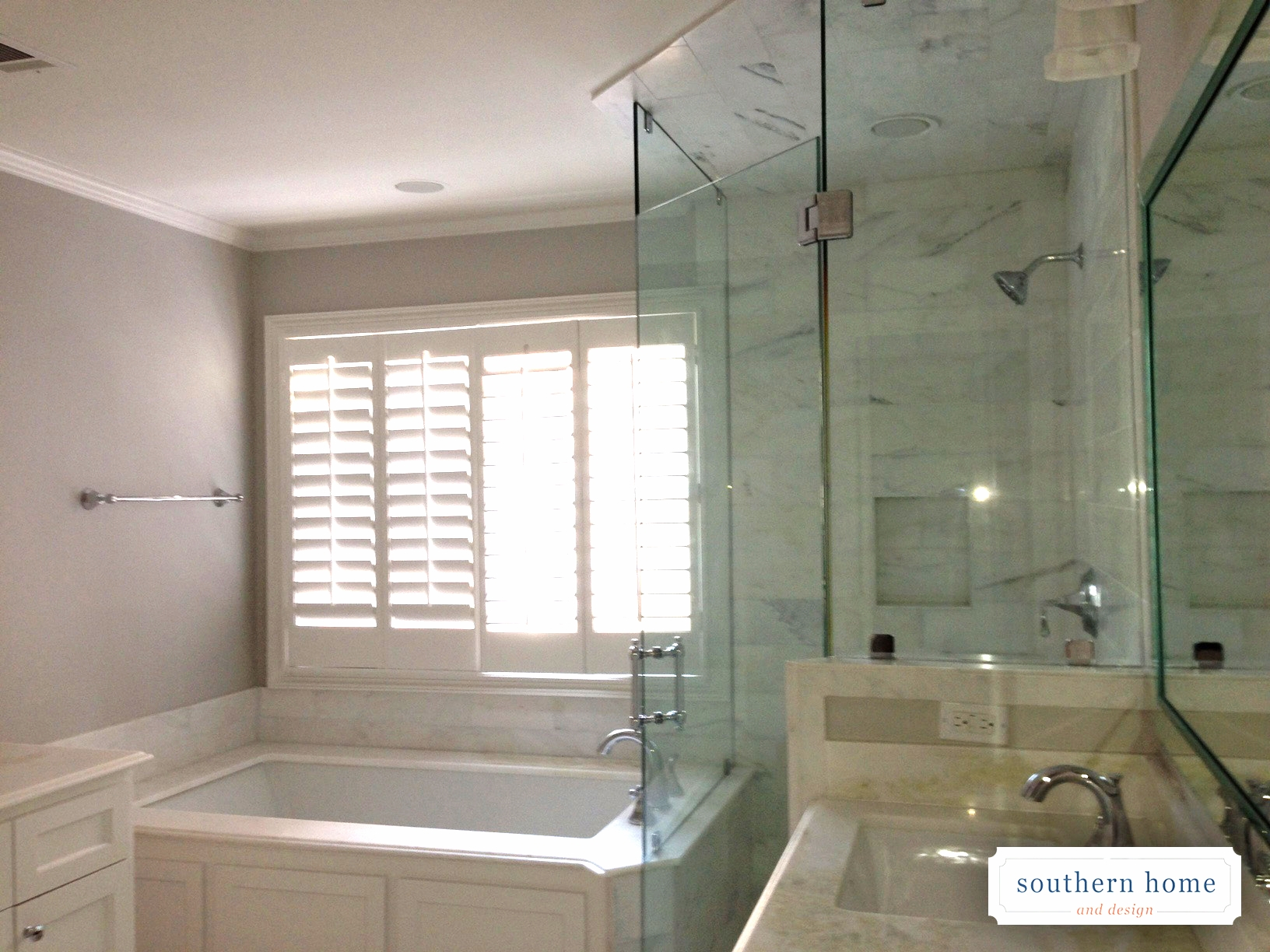 Clean, modern bathroom design in Dallas. Enclosed glass shower, shutters, and white tub.
