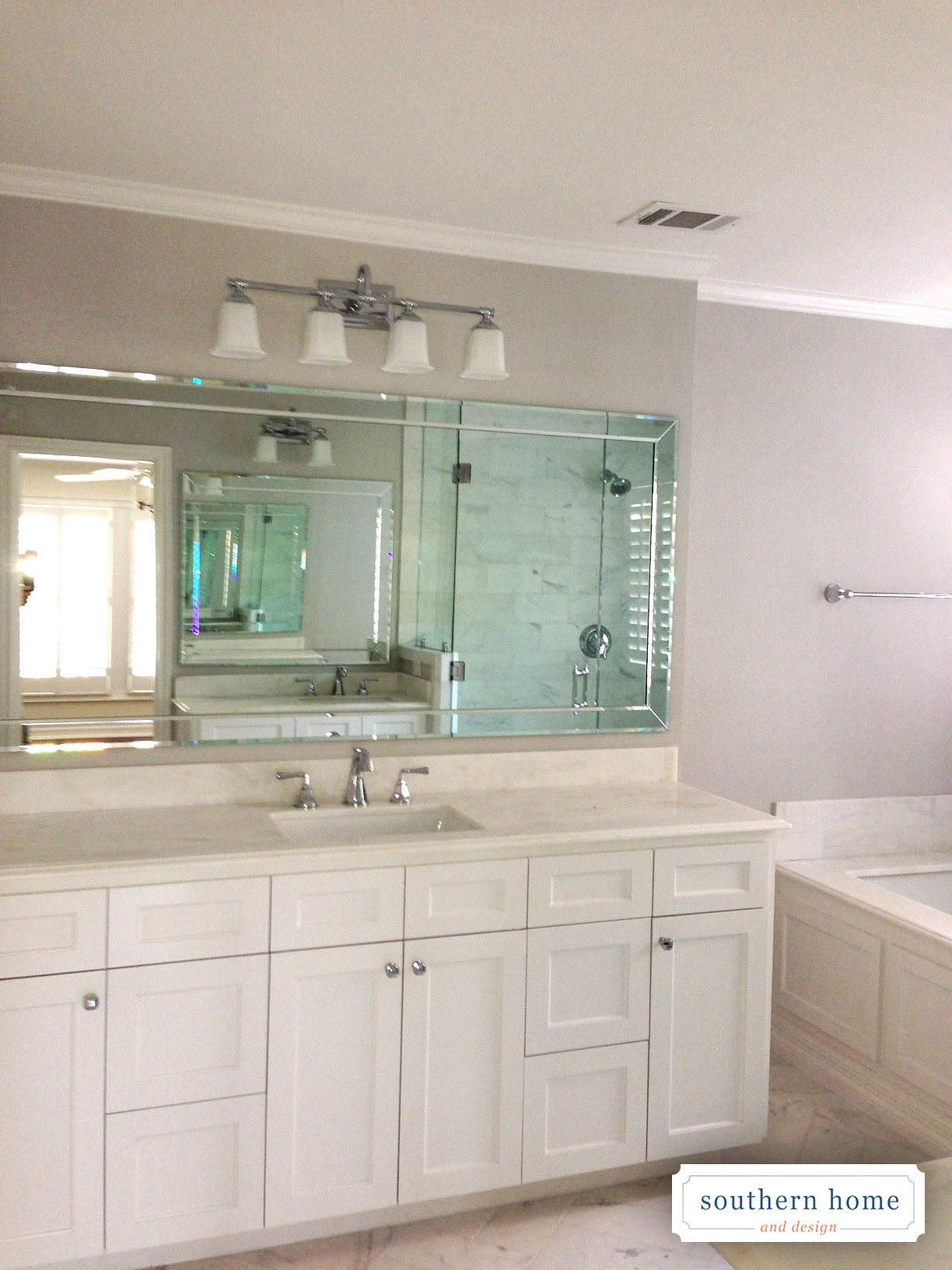 Custom bathroom in Dallas. White shaker cabinets, beveled glass mirror, and chrome accents.