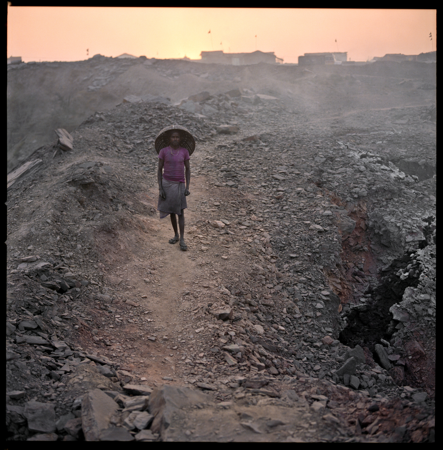 THE BURNING CITY JHARIA, INDIA | 2009-2012   Ever since I was a child, I have heard that Eskimos have dozens of different words to describe subtle nuances of white. When I arrived in Jharia, I couldn't help wondering the same thing about the inhabitants of the largest mining area in India. Could these people have developed a special vocabulary for all the nuances of black? Roughly 400,000 live in Jharia. The lunar-like soil hasn't produced vegetation for a long time and won't be doing so any time soon. But the main danger for local inhabitants does not come from the black dust that is permanently floating in their environment. The danger is deeper and it is developing under their feet in the heart of coal seams. Bad management of the mines has led to uncontrolled underground fires. Over more than a century, millions of tons of coal have burnt up. It is equivalent to a volcano growing under Jharia. Toxic gas vapours spread into the atmosphere, the ground is sinking and houses are starting to crack. Sometimes flames burst up by the roadside. The imminence of a human disaster is very real. The Indian government is aware of this but doesn't seem to want to free up enough funds to relocate the population at risk.