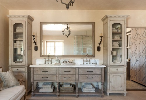 French farmhouse style bathroom with rustic sconces and chandelier.