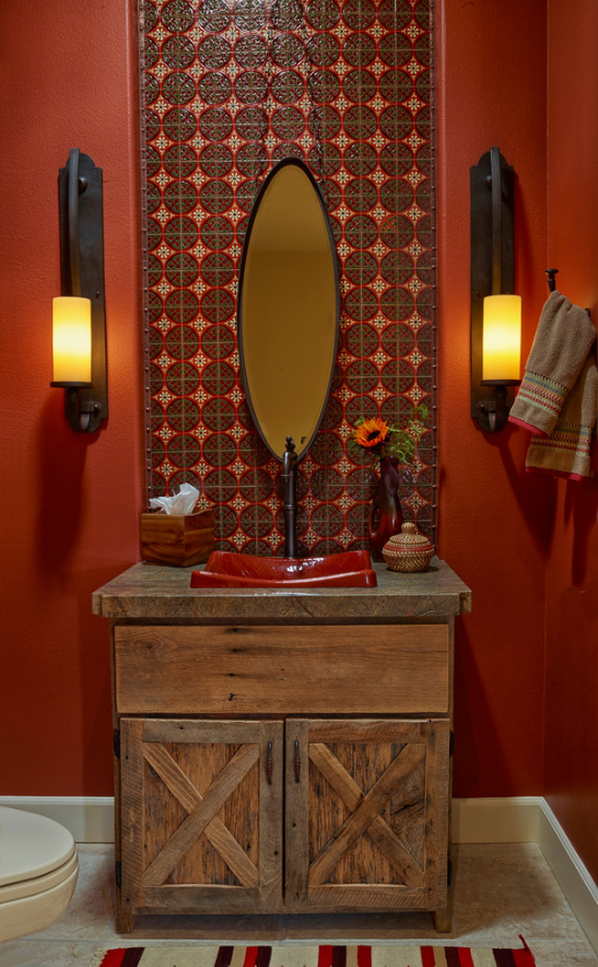 A bold, vibrant bathroom with electrified candle sconces.