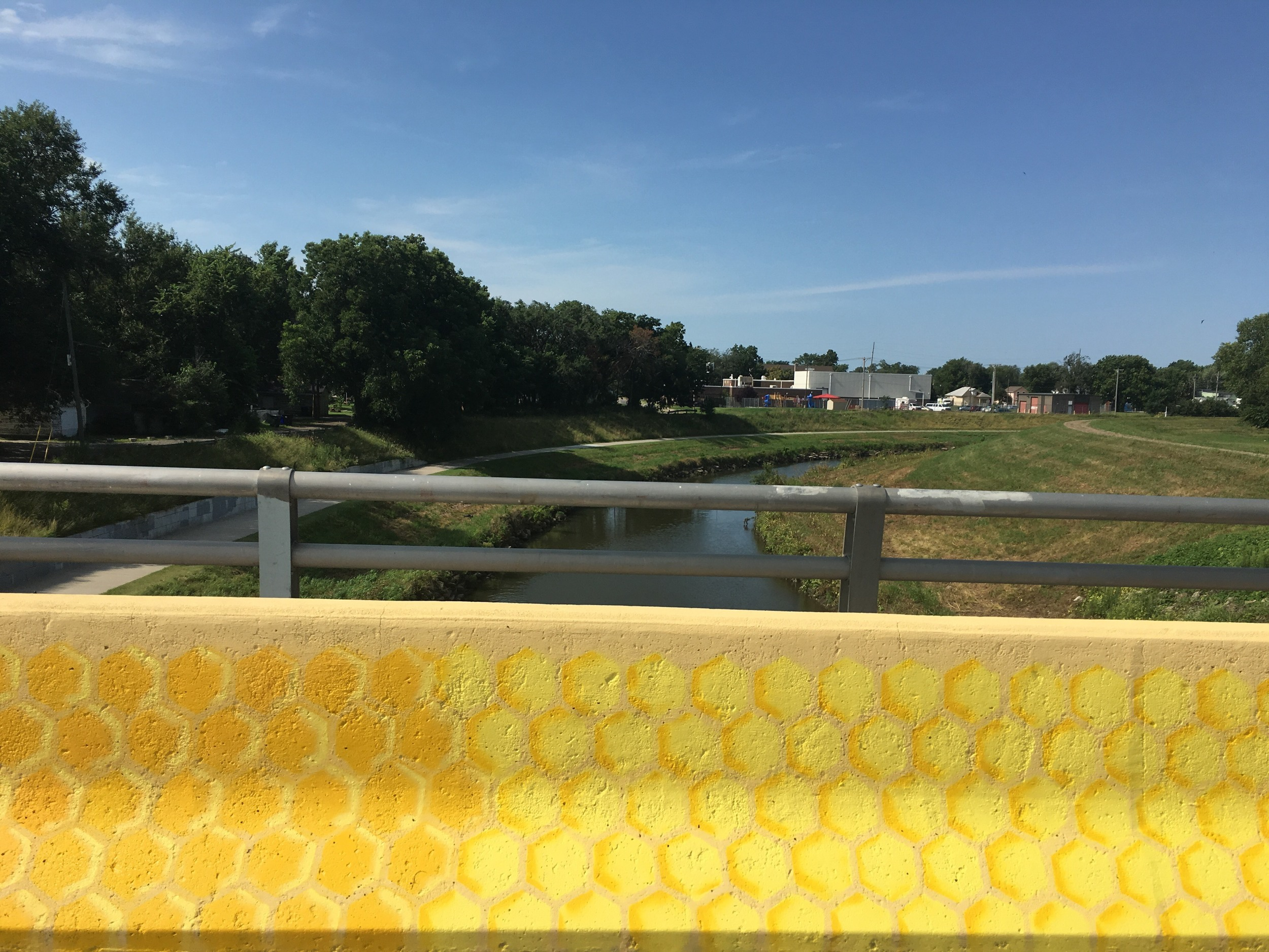 The traffic side of the bridge displays a honeycomb pattern, which references the stream below as well as the structure and community which are hallmarks of a hive. -