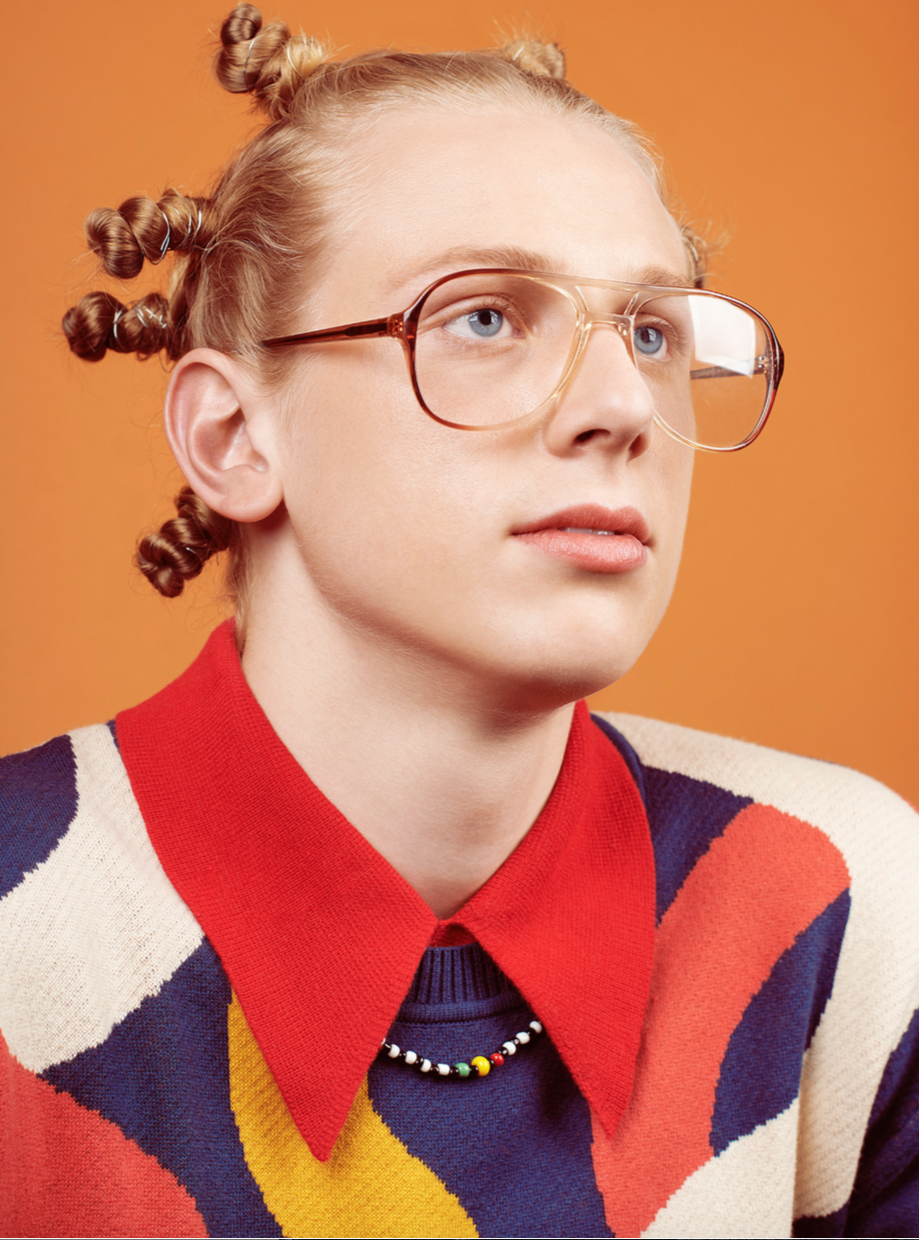 Hans (D-1, NYC)    Photography: Timothy Smith /  @timothy_smith_     Makeup: Jake Aebly /  @makeupbyjake    Sweater:  Henrik Vibskov   Shirt: Vintage  Necklace: African Market, Harlem   Glasses: Vintage