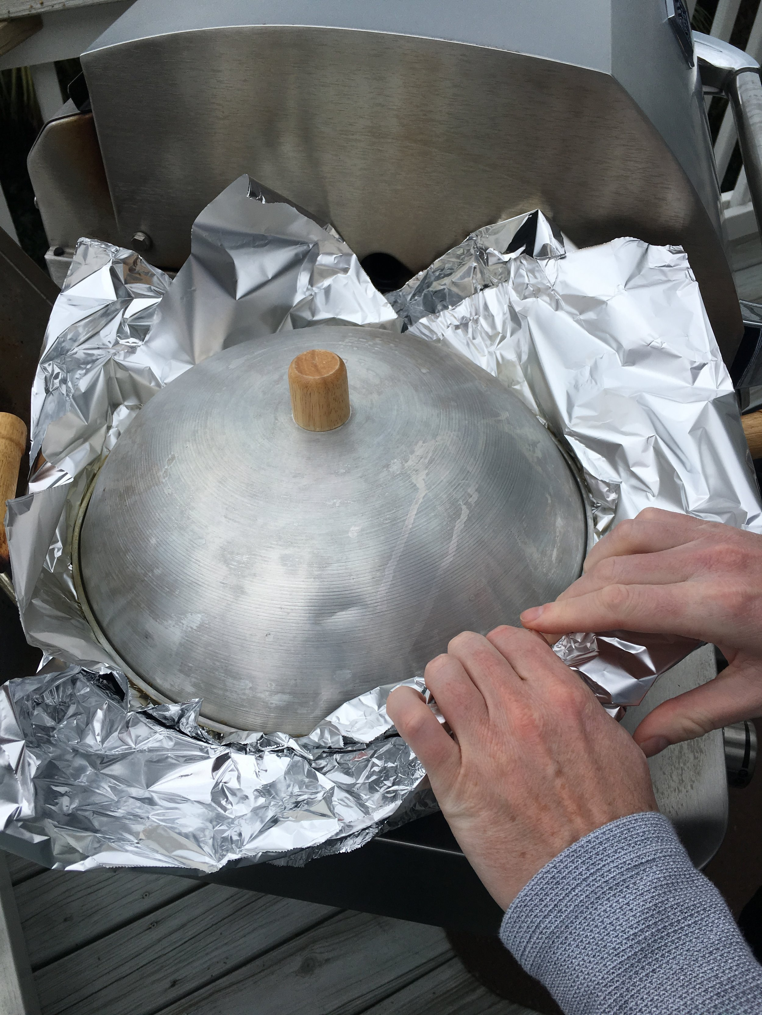 Once you see some wisps of smoke, pop that foil-lined lid on top of your wok and quickly (and carefully!) roll and crimp the two layers of foil together to form your seal.