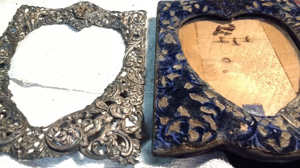 A slide by side comparison of the sterling silver frame next to the fabric wood frame.
