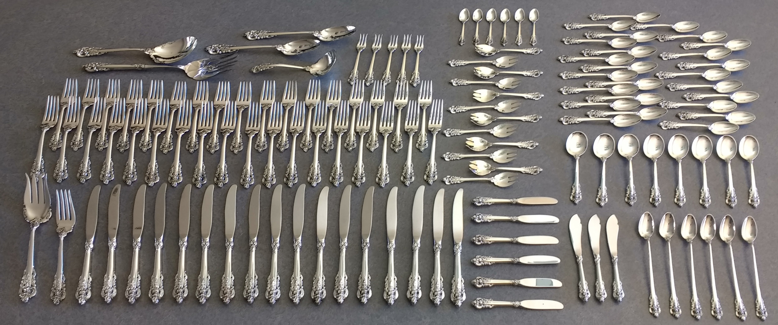 Sterling silver knives, forks, spoons, and serving pieces.