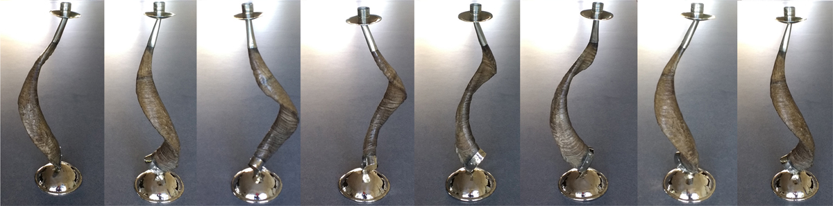 multiple views of unusual Ram's Horn Candlestick with silver base