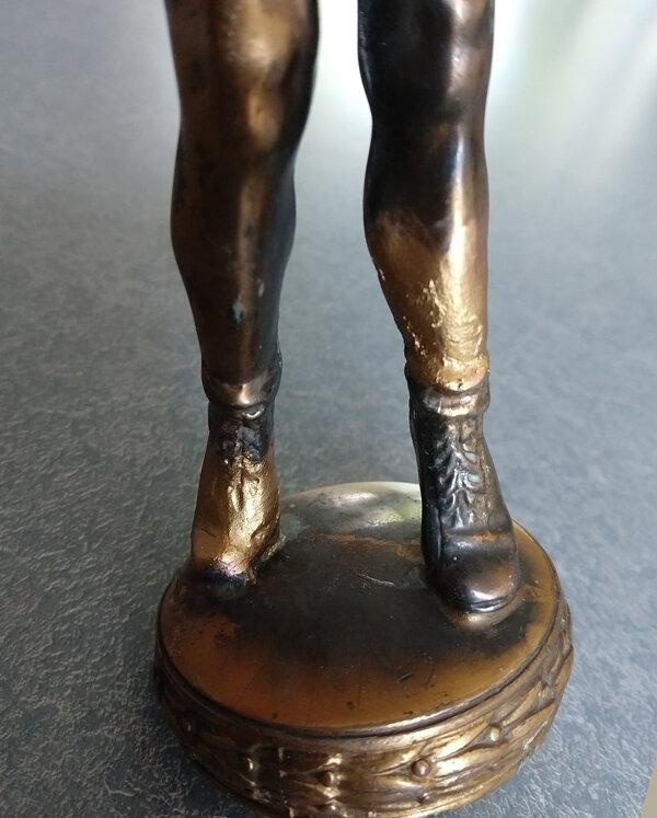 First coat of paint repairing an athletic figure trophy
