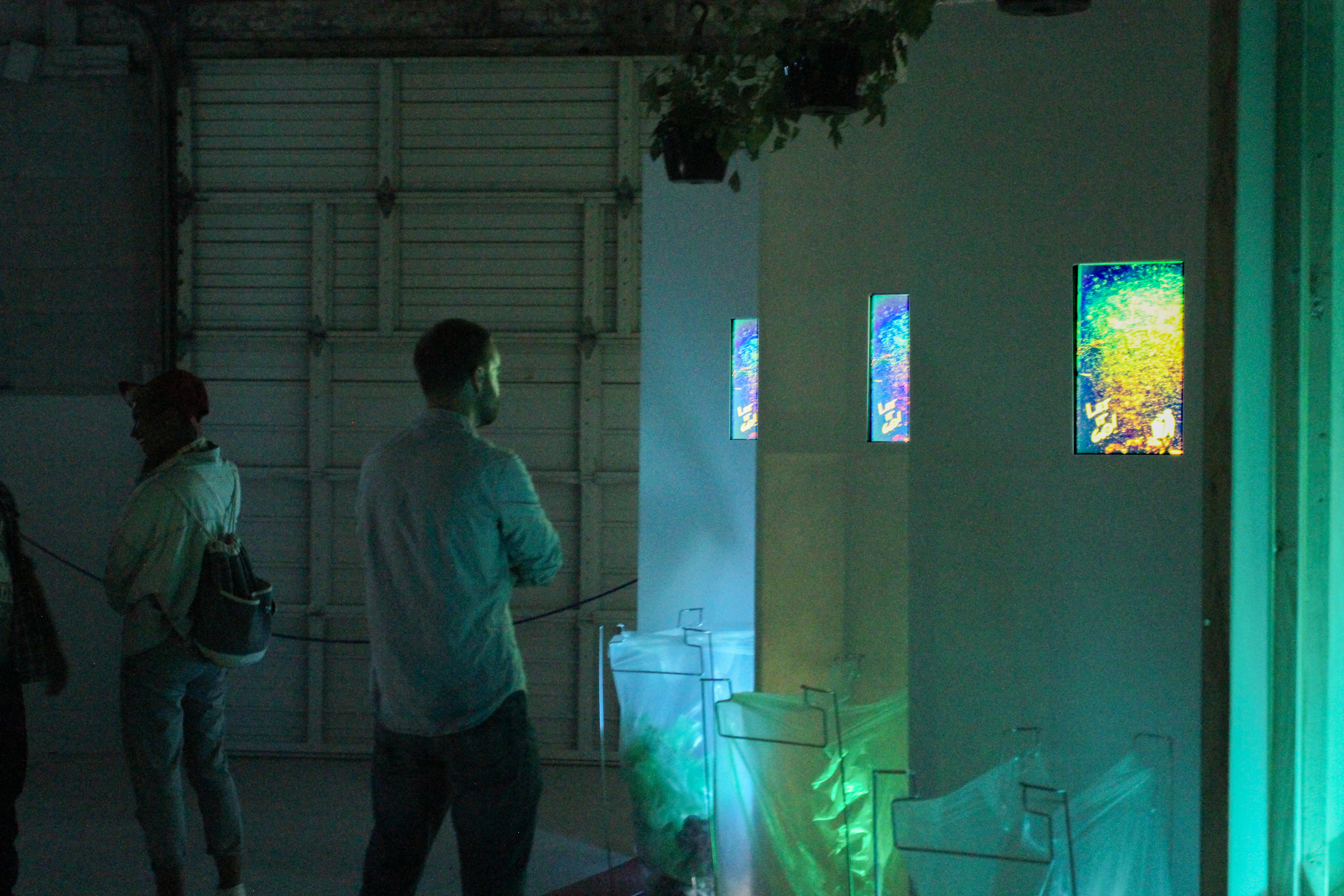 Shakedown   Dave Greber. 2016. Wood, GatorPlas, (3) flat screen monitors, HDMI media player, looped video (3:41m), speaker pendant and amplifier, (3) ivy plants, three lamps Dimensions: 15 x 5 x 8 feet