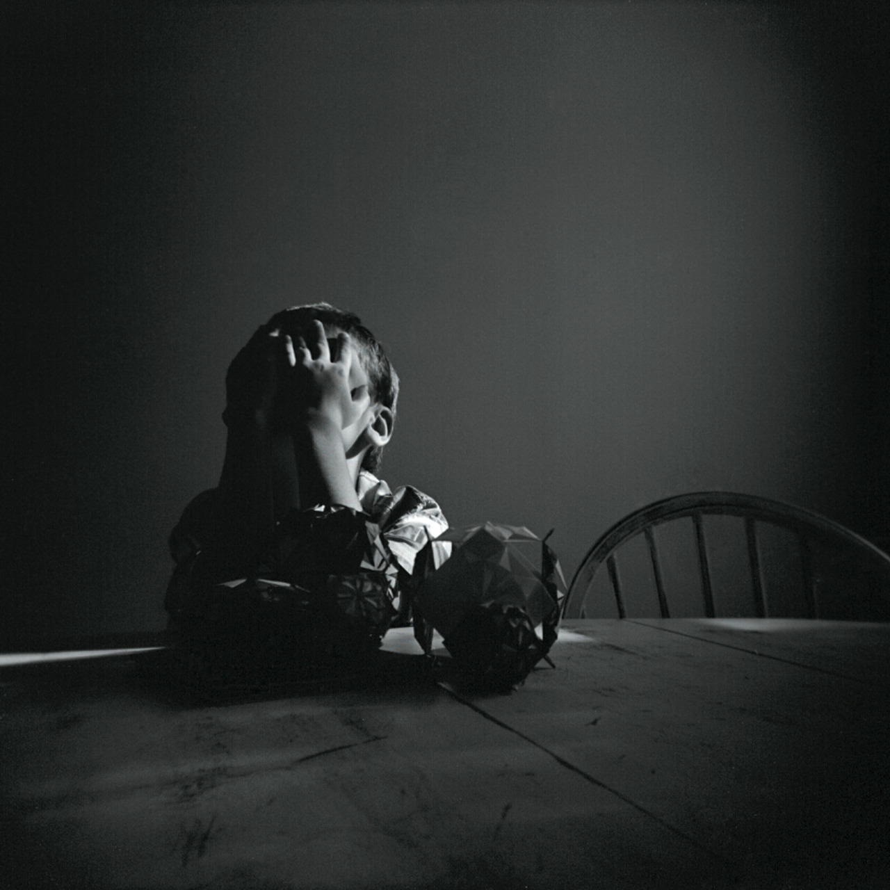 Xander at the kitchen table, showing me how he feels about his post Kusudama kickstarter production schedule.   Holga, Tri X 400