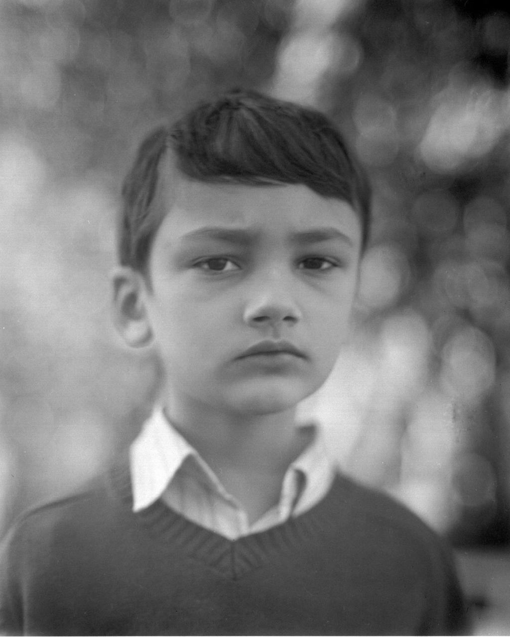 This is an overexposed image of Xander shot on tri-x 320 using my 4x5. I sent this out to be processed and scanned the negative with my Epson V700.   One of the draw backs to my 4x5 is that the lens has no shutter, so all exposures are manual. Actually, I think I should rephrase that and say the draw back is that I'm not experienced enough with the lens/camera combo to know what I'm doing…yet :)   This was taken in the middle of the afternoon under the shade of many trees. At the moment I have a box of tri-x 320 and so I set the aperture to f/11 and metered for those setting. Of course the suggestion was about 1/36 which is not possible without a shutter. At the time I had completely forgotten about pushing/pulling film so I just used my hand and covered/uncovered the lens as quickly as I could and sent it out to be processed fully expecting total failure. Results? You guessed it, way over exposed.   I still think it's lovely. It has that antique glow to it doesn't it? Most importantly I knew what I was doing wrong and I know how to fix it. I think a slower speed film is in order as well as testing out some filters. While I'm waiting for my order of t-max 100 to come in I'm going to try pulling the 320. *fingers crossed*