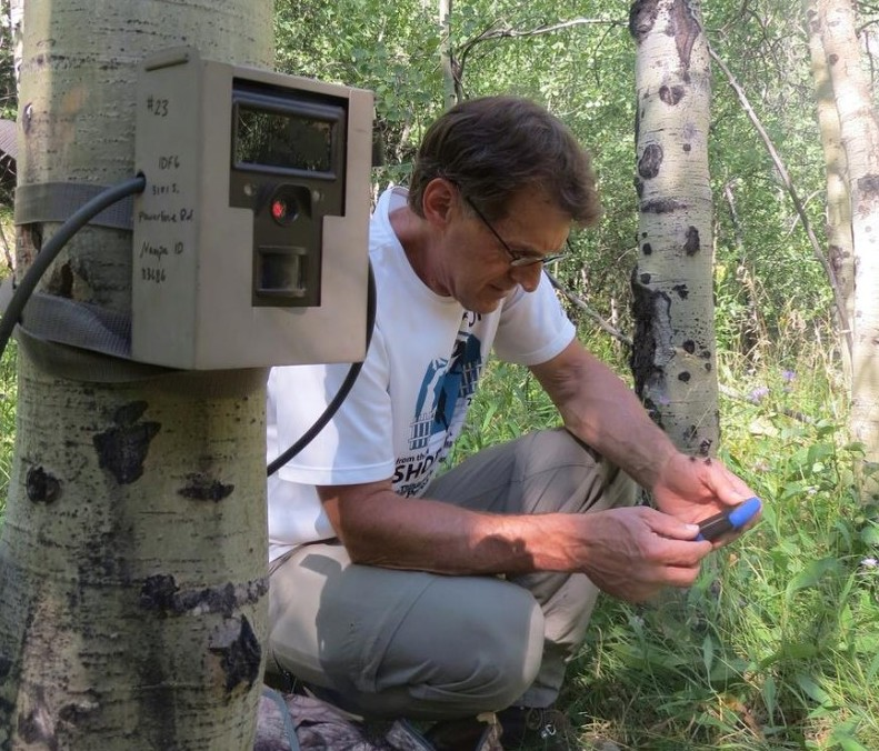 Kris Thoreson, the WRWP Field Manager, setting up a camera trap and recording the GPS coordinates in the Project Area.  Photo Credit: Lauren Hennelly