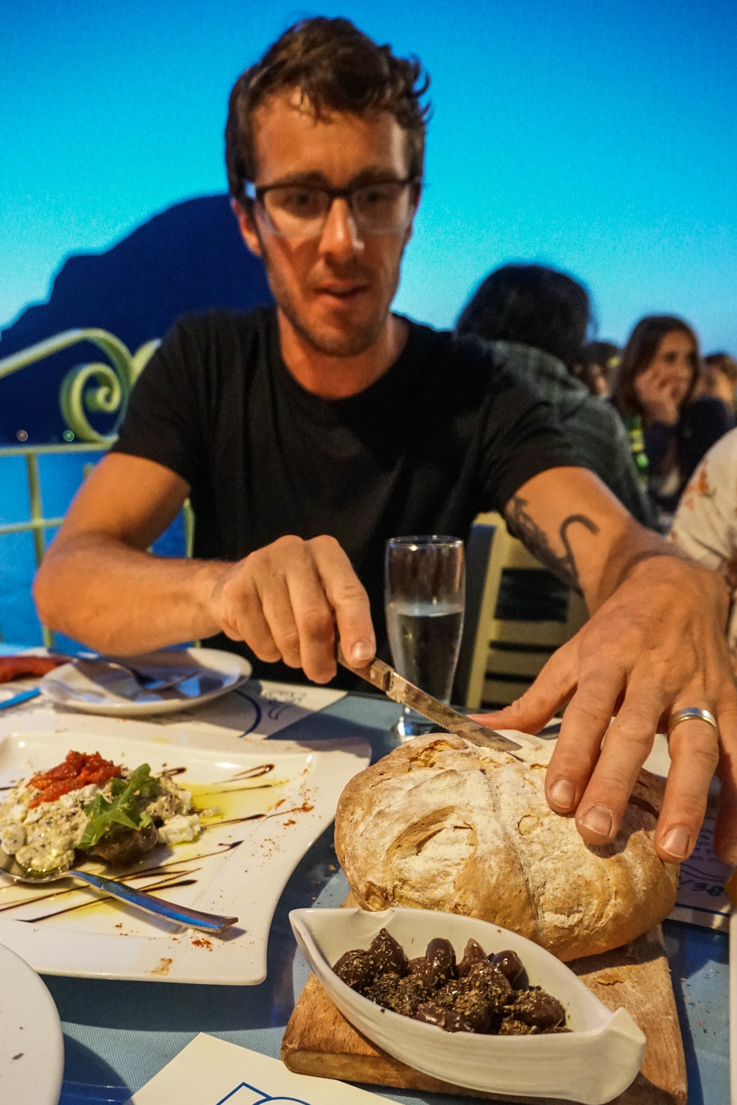 Michael cutting into fresh baked bread at the Aegean