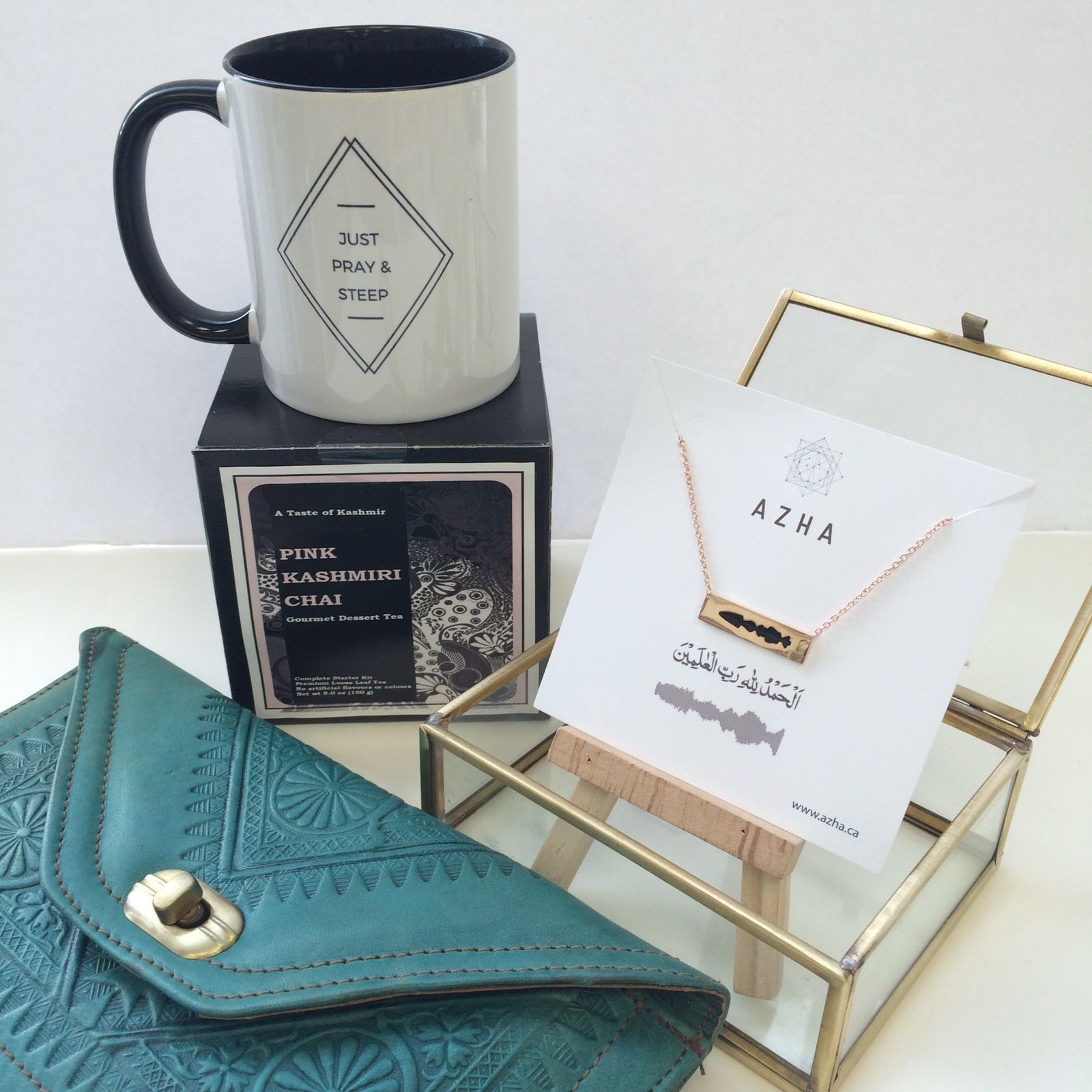 "Aneesa's gift for her mom, Safia. Just Pray & Steep Mug (Eastern Toybox, $15), Kashmiri Chai kit (Zaza & Umbairo $13.50), Leather Moroccan Clutch (Al- Kahf $45), Rose Gold Dipped ""Alhamdulillah"" Necklace (Azha $60)."