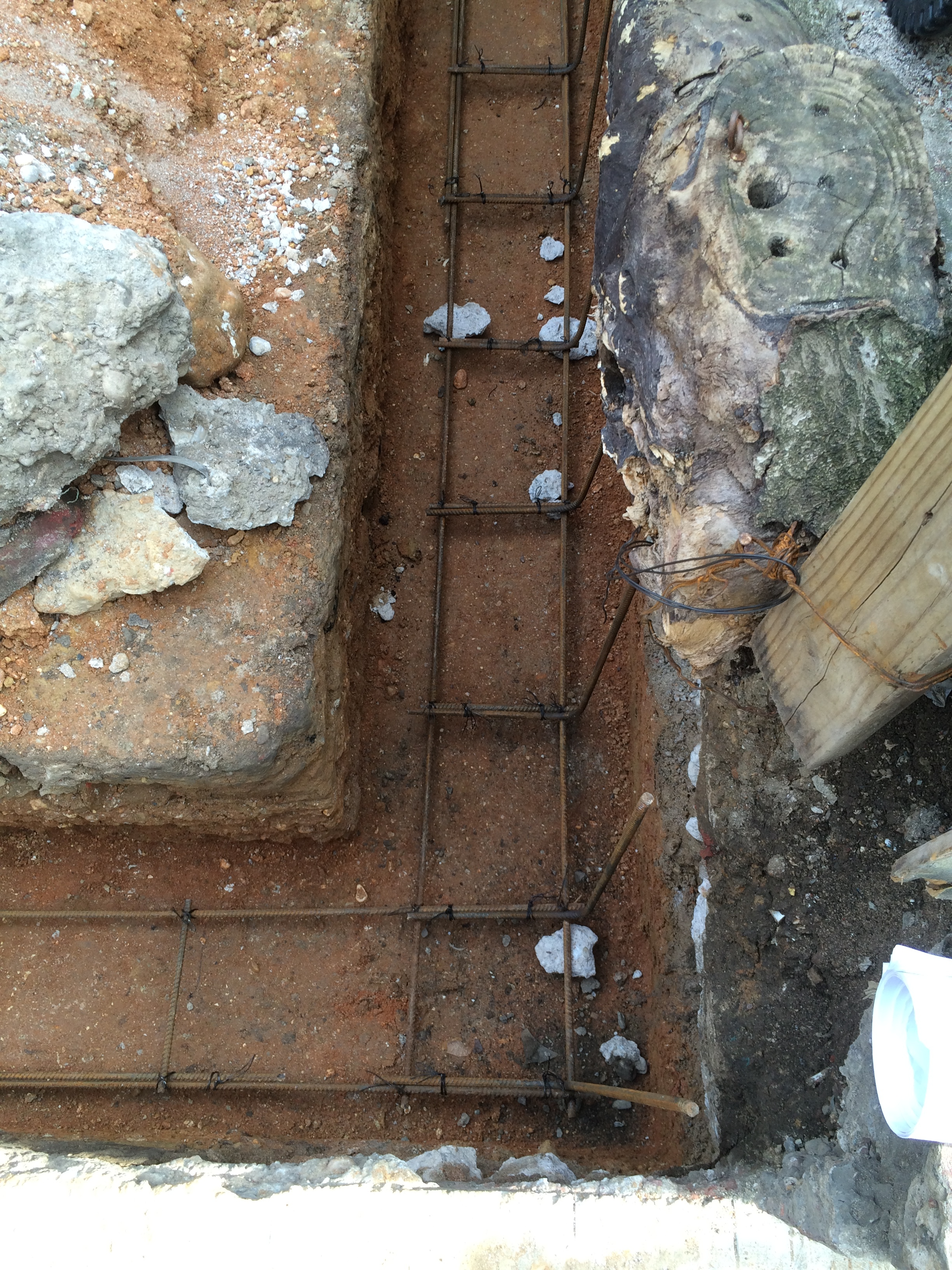 Trench for the new garage foundation wall ready for concrete to be poured (with steel re-bar installed).