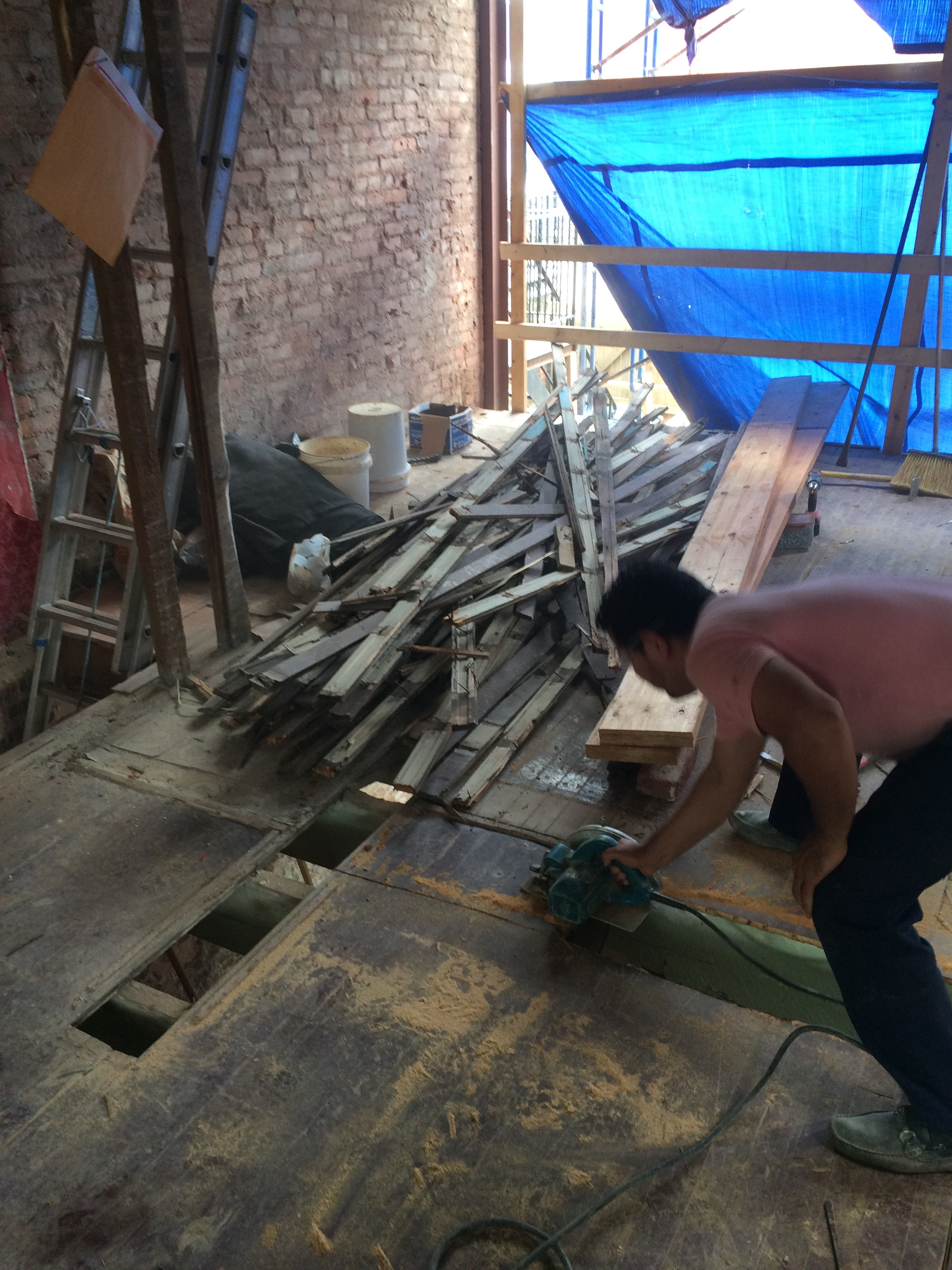 Removing a section of the old subfloor to create a space for installing the new beam in the floor framing