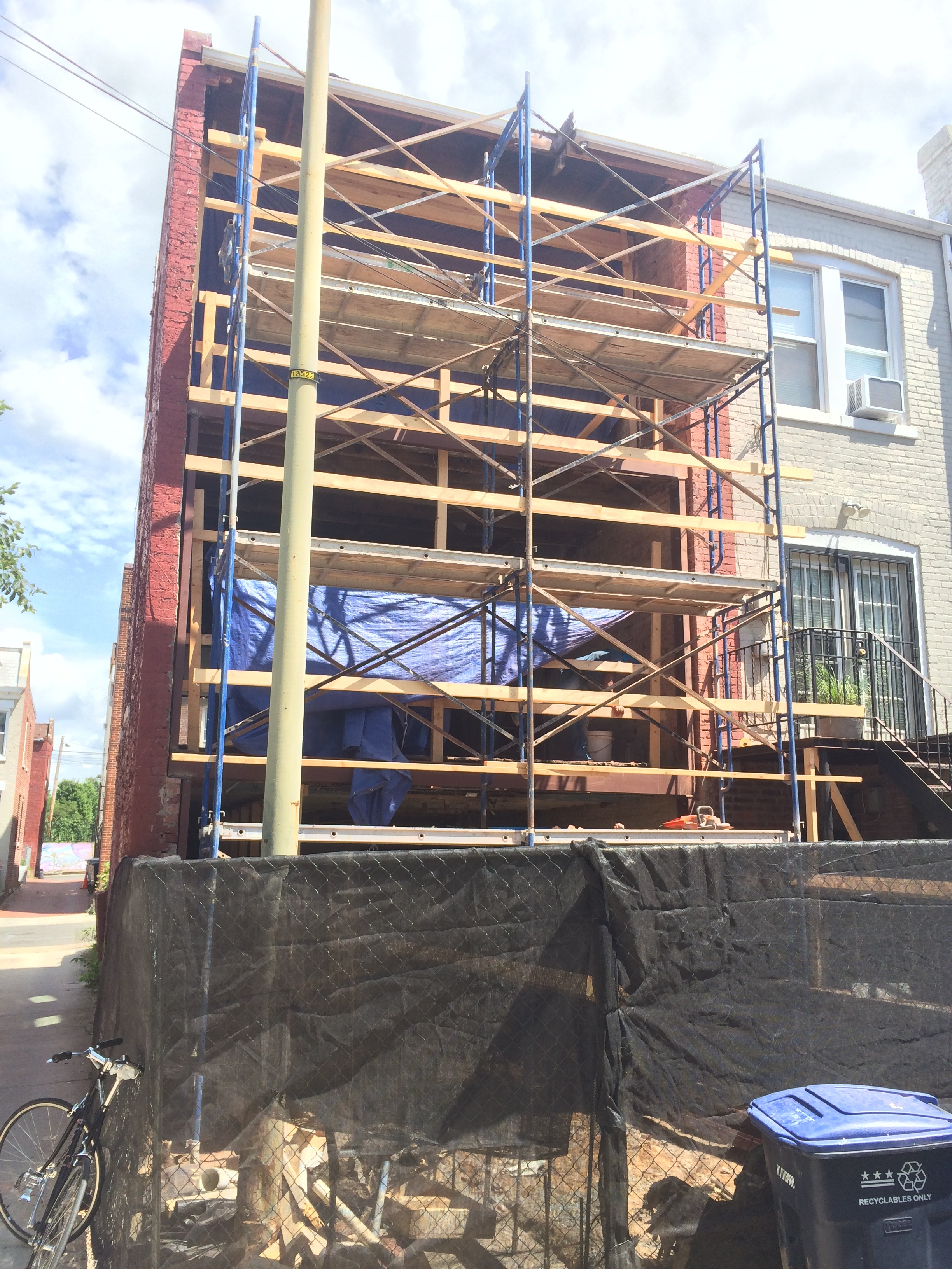 View from rear alley showing scaffolding during installation of steel frame.