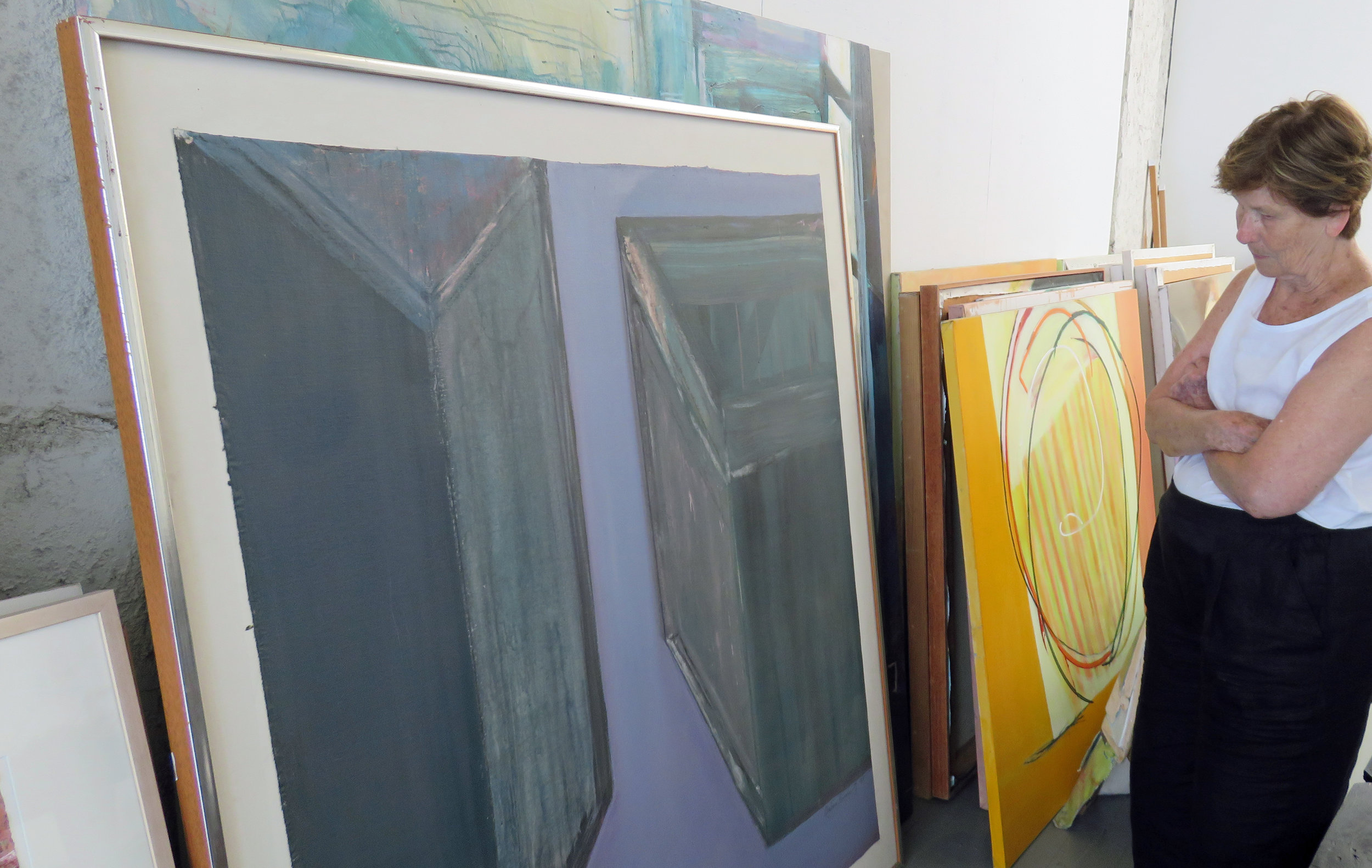 Barbara Hirschowitz looks over some of her large paintings stored in her studio.