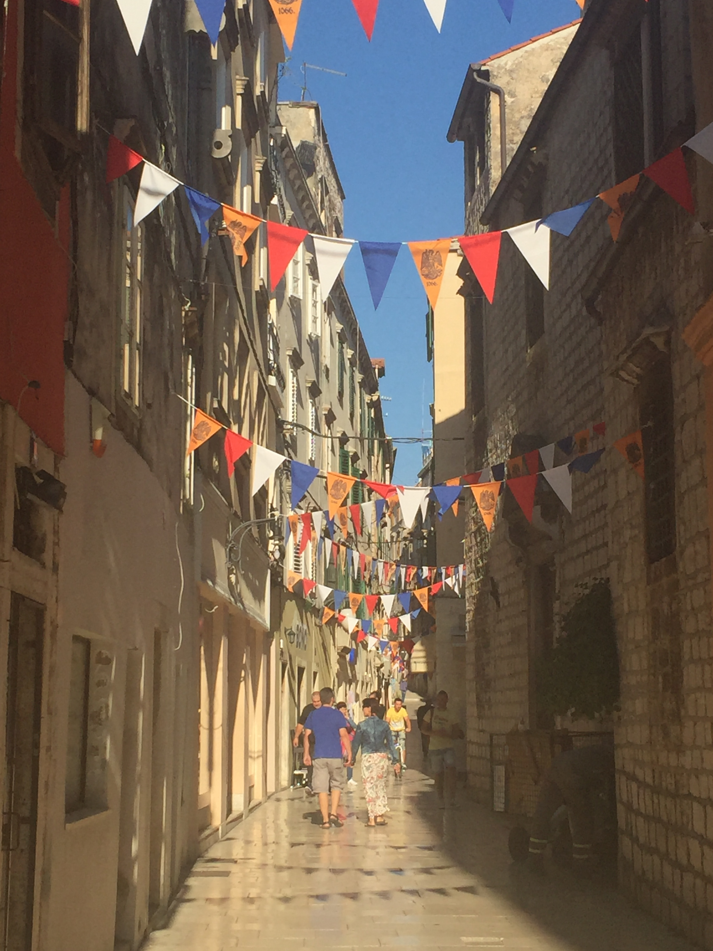 An old street leading to the central piazza adorned with banners celebrating the town's 950th birthday. The golden hued tempera of the Dalmatian marble was evident everywhere and gives the city a very royal look and feel.b