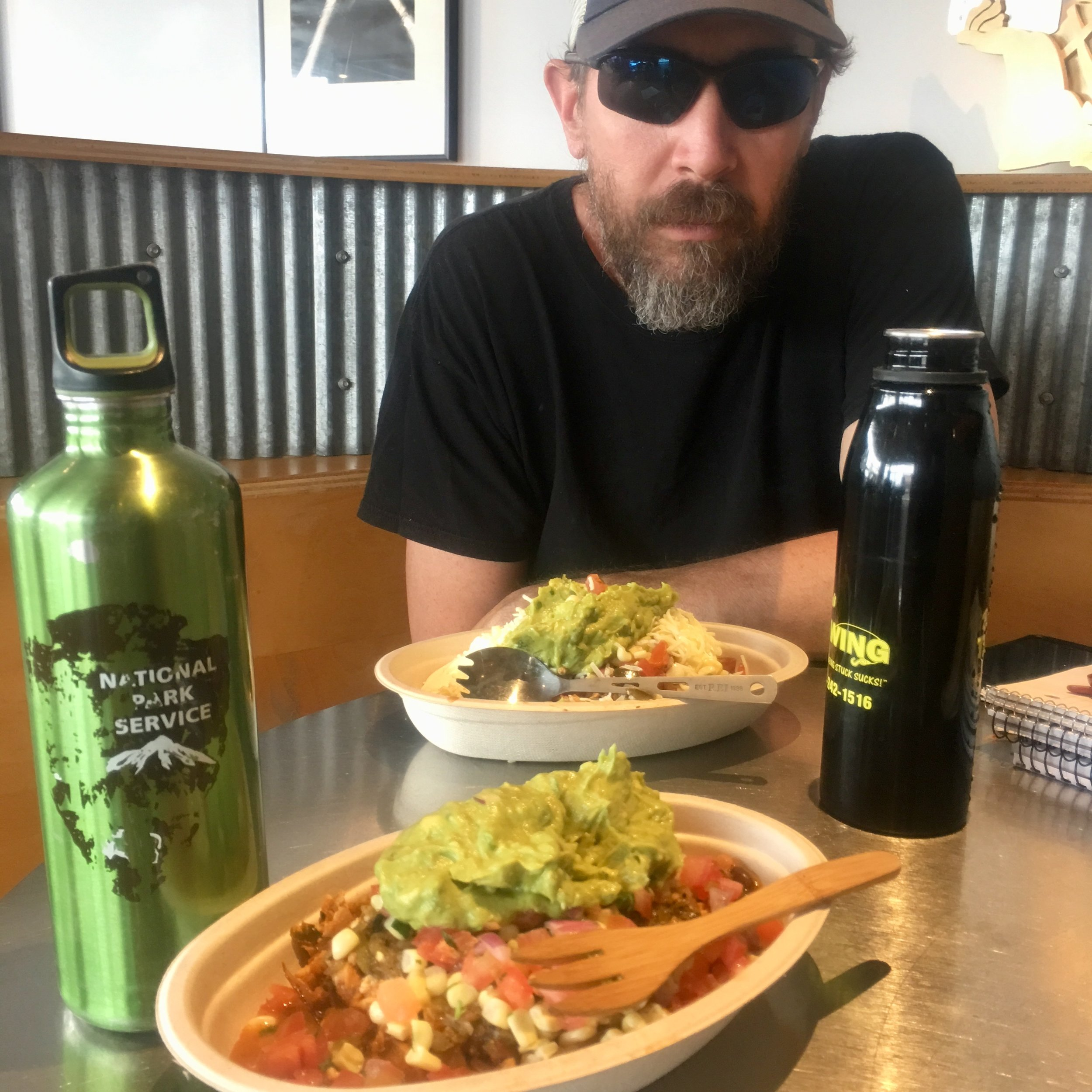 Adam at lunch today with my bamboo To-Go Ware fork, his titanium REI spork, our yummy Chipotle Sofritas bowls (mine is vegan, his is veggie),and our respective water bottles.