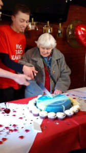 Life-long resident Sheila Taylor joins her adopted activist Sam in cutting the cake.