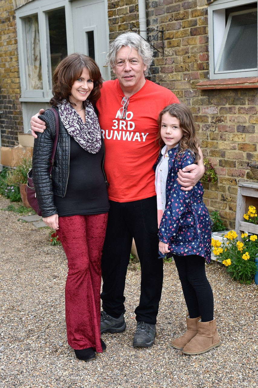 Neil outside his home with his partner Emma and daughter Millie