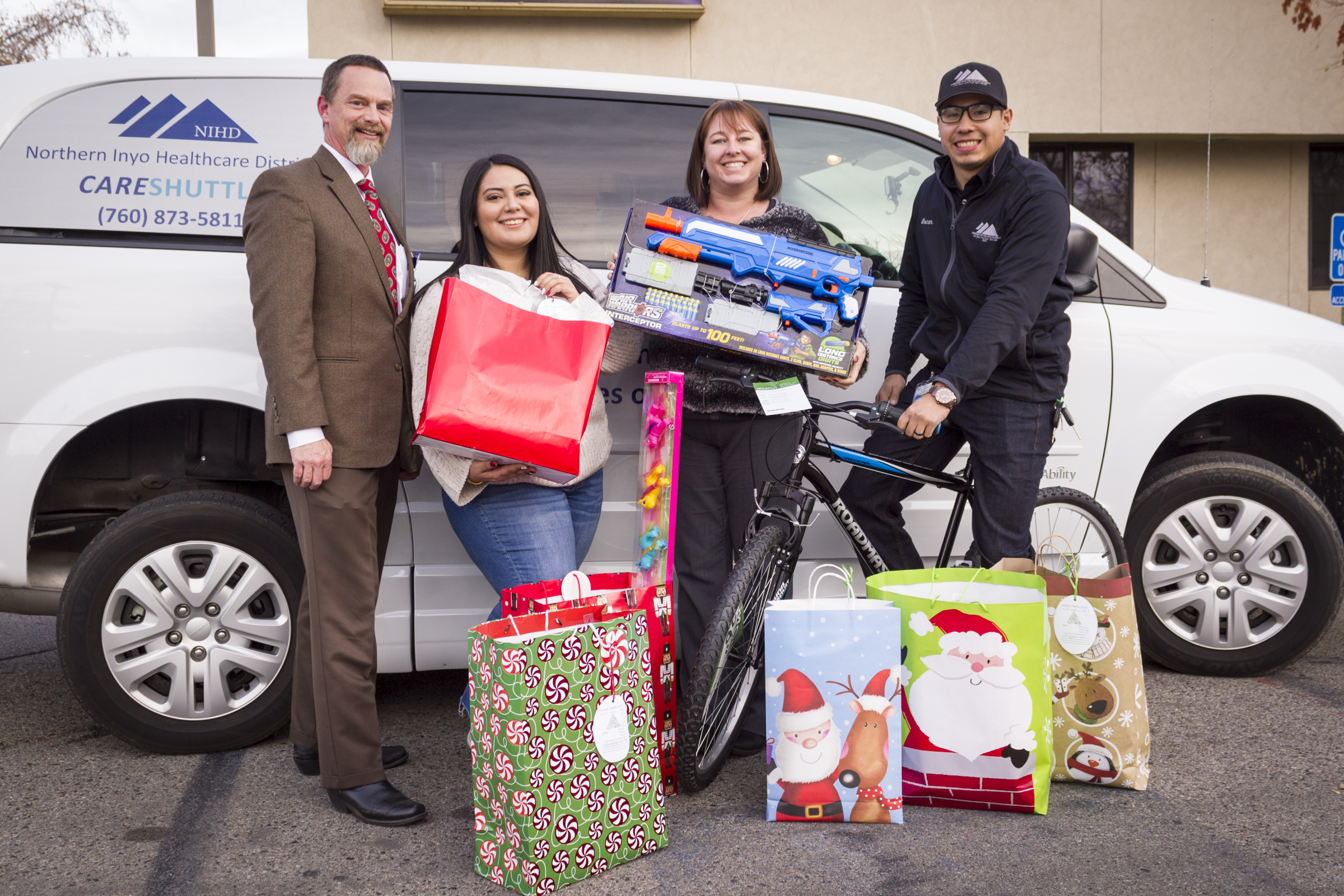 Wish Tree Delivery:  The employees of Northern Inyo Healthcare District made a difference in the Christmas holiday of 47 local children with their annual holiday gift drive for IMACA's Wish Tree program. Shown here with a sampling of the gifts provided are, from left, NIHD CEO Dr. Kevin S. Flanigan, Michelle Garcia, Kristen Bernasconi and Oscar Lopez-Esparza.  Photo by Barbara Laughon/Northern Inyo Healthcare District