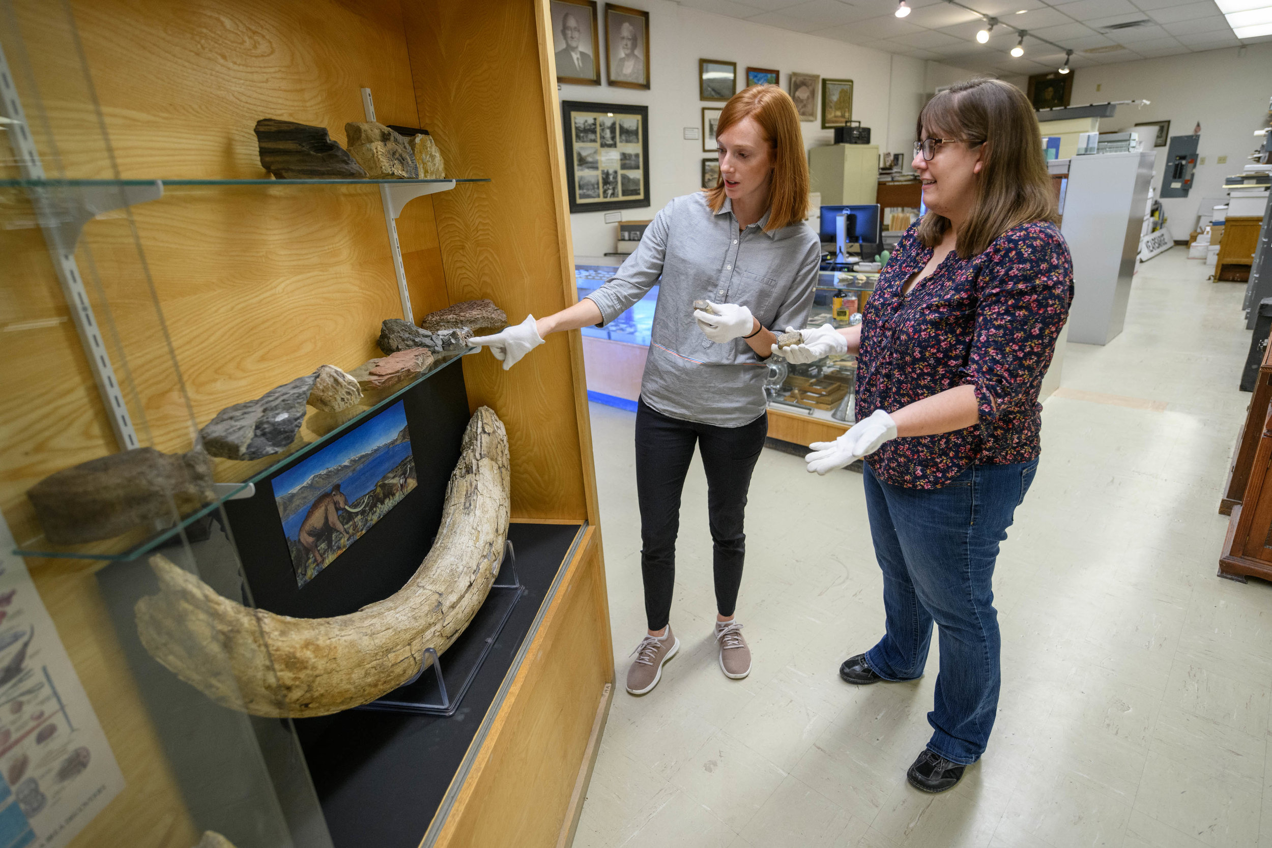 Jessica Johnson, LADWP Public Relations Specialist, left, and Heather Todd, Eastern California Museum Curator of Collections and Exhibits, examine the specimens in the museum's Fossil Case, which includes the recently installed proboscidean tusk and artwork. Photo courtesy LADWP
