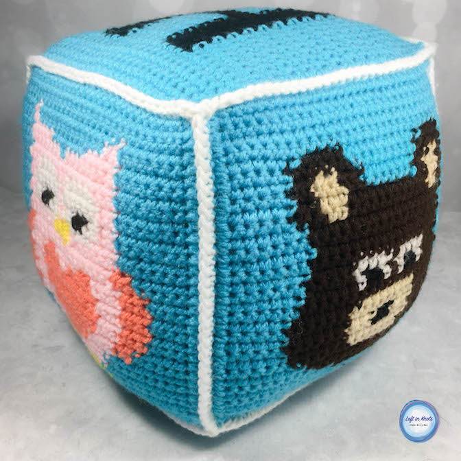 If you've been following along with my all week, you have seen my recent Grids for Kids crochet block project. If you haven't, make sure you check out the free patterns for my Fox, Bear, Raccoon, and Owl squares! In this post I'm going to show you how I put these squares together to make a giant pillow block perfect for babies.