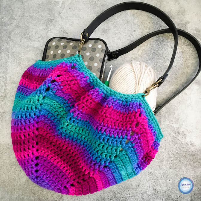 This little bag is one of the easiest things you will ever crochet! Why? Because it is literally one big, solid granny square, takes only one skein of yarn, and the yarn does all of that beautiful color stripe work for you! When you are done you will have just two ends to weave in and a beautiful bag perfect for carrying around your latest WIP. Today's free crochet pattern is the Twilight Stripes Fat Bottom Bag and it features the new Red Heart Super Saver Stripes yarn! Keep reading for the free pattern.
