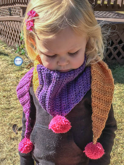 """My """"mod scarf"""" patterns are some of my favorites, so I decided to make a mini version for my daughter! This simple and modern scarf is adorned with pom poms and is perfect for children. Keep reading for the free crochet pattern."""
