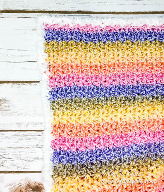 This crochet blanket is perfect for a fast and easy baby blanket, but it can also be sized up to be a throw or afghan. Beautiful self-striping yarn combined with the lemon peel stitch make this blanket colorful with wonderful texture. This free crochet pattern is easy and suitable for beginners and experienced crocheters alike.