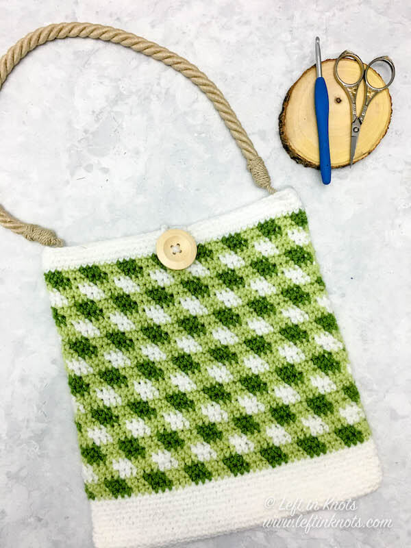 This free and easy crochet pattern uses simple color work to create a modern crochet market bag with gingham or plaid print. This project is an easy stash buster pattern and uses less than one skein of each color. Attach a farmhouse-inspired rope handle or crochet your own for a finishing touch!