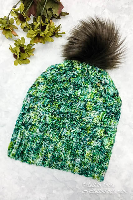The Monteverde Slouchy Hat is a one skein project that features bobbles and just a bit of filet stitching. This free pattern is easy and fast to make. Use a special skein of hand dyed yarn or any light worsted weight yarn; then top it with a faux fur pom for a modern touch.