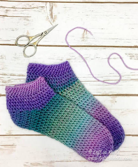 This free crochet pattern uses less that one skein of yarn to make easy crochet slipper socks. Use Lion Brand Ferris Wheel yarn to create a beautiful colorful gradient in brights or neutrals. Or if you prefer, substitute your favorite Category 3 yarn and make these simple slippers in easily adjustable sizes.
