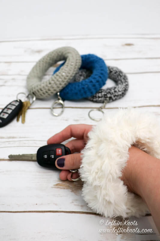 The Crochet Bangle Bracelet O Key Ring is a fast scrap buster pattern that is a perfect DIY make for gifts or craft fairs. Use faux fur yarn, bulky yarn, worsted yarn - or anything else you've got leftover in your yarn stash. This crochet bracelet key ring is a game changer when it comes to keeping track of your keys and will be loved by busy moms everywhere!