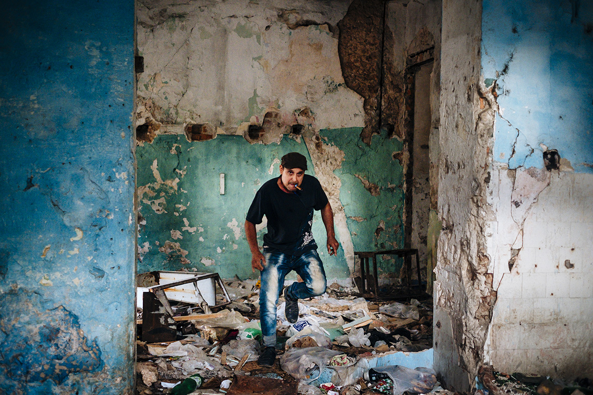 A man smoking a cigar leaves the ruins of a building after pissing in Havana Vieja.