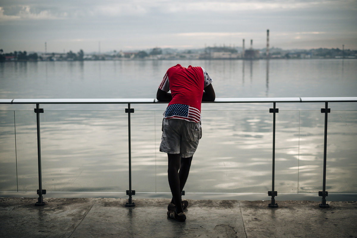 A young boy dressed in a US flag t-shit waits for the boat at the ferry terminal in Havana Vieja.