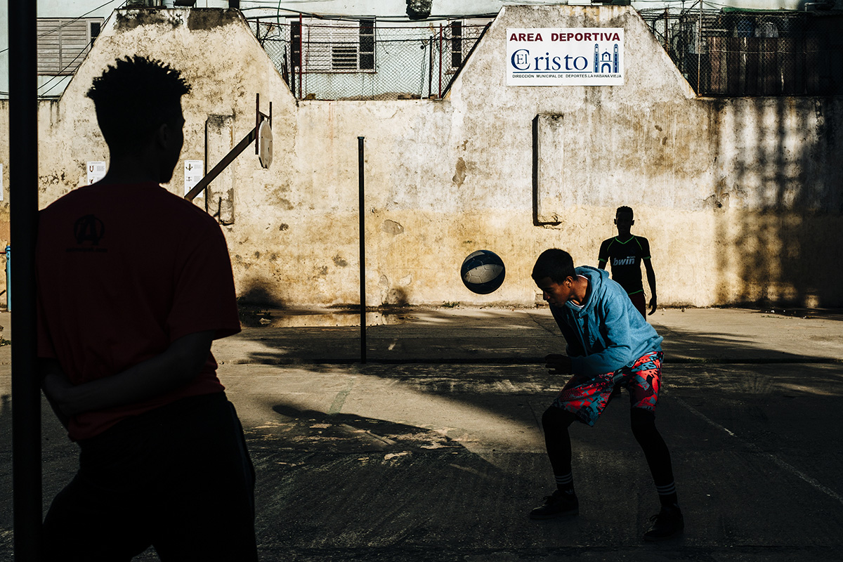 Boys play football at a public sports court in Havana Vieja.