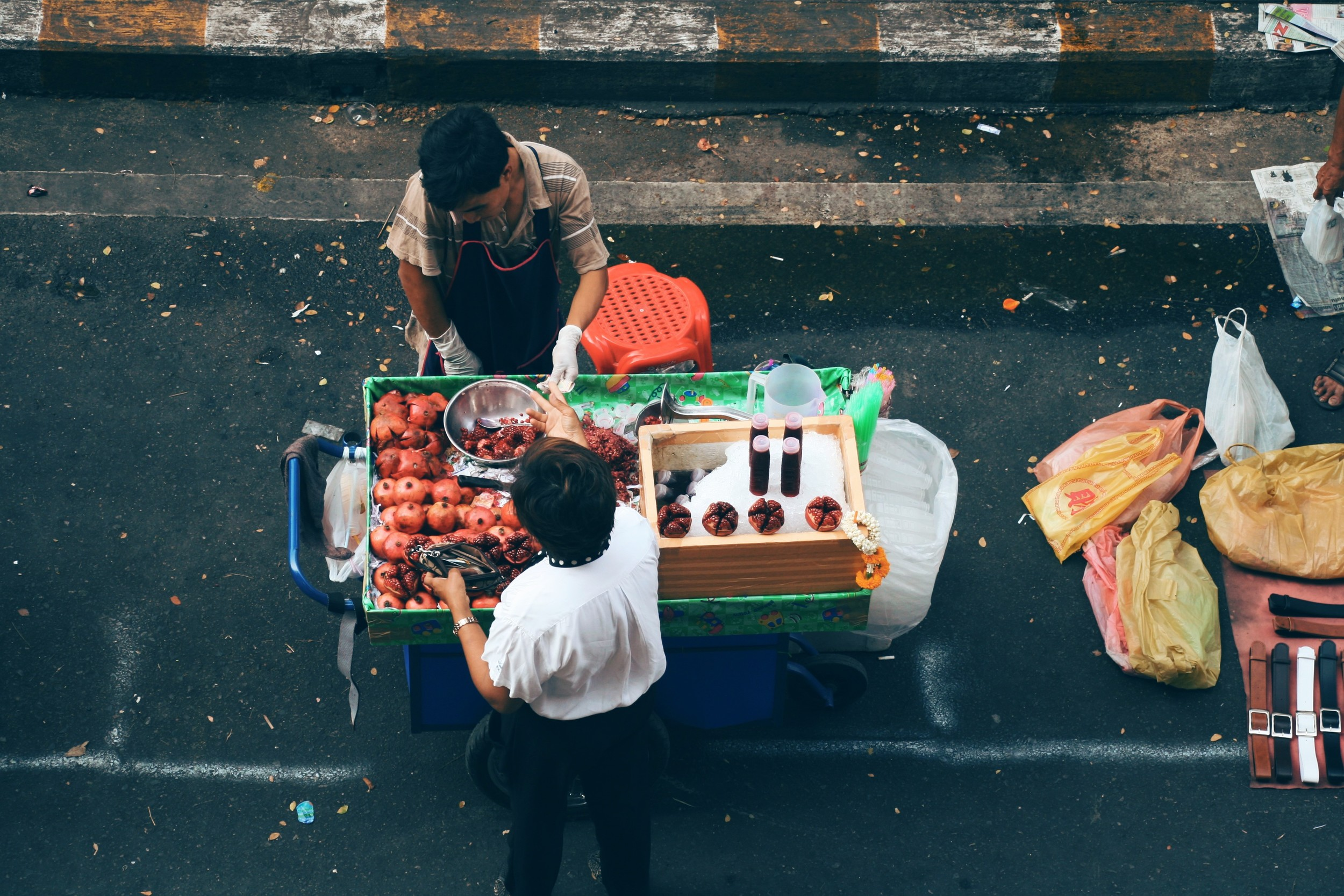 Fresh fruit vendor selling whole pomegranates or juice in a bottle
