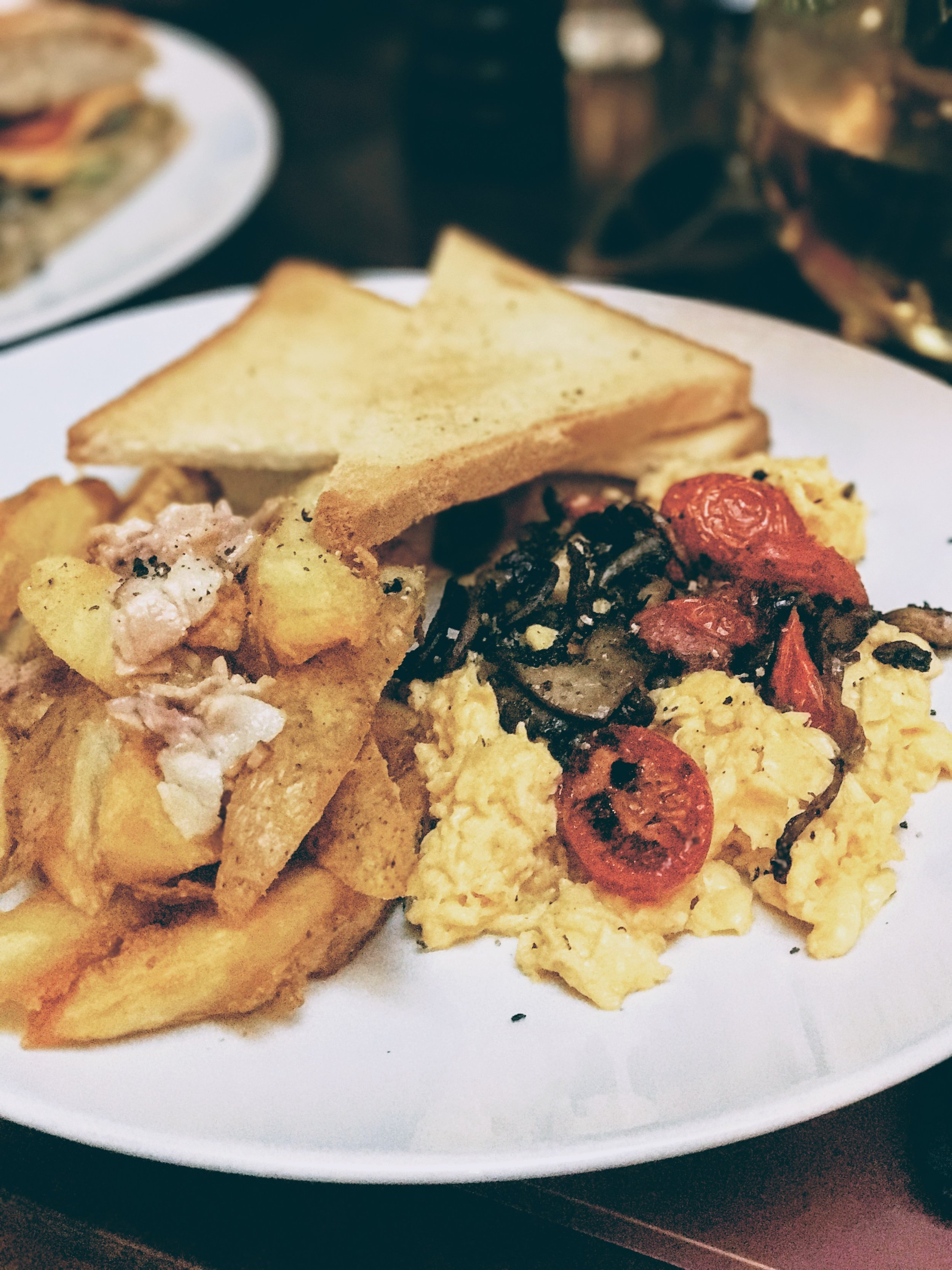 Scrambled eggs with cherry tomatoes and mushrooms - served with crunch country-style potatoes