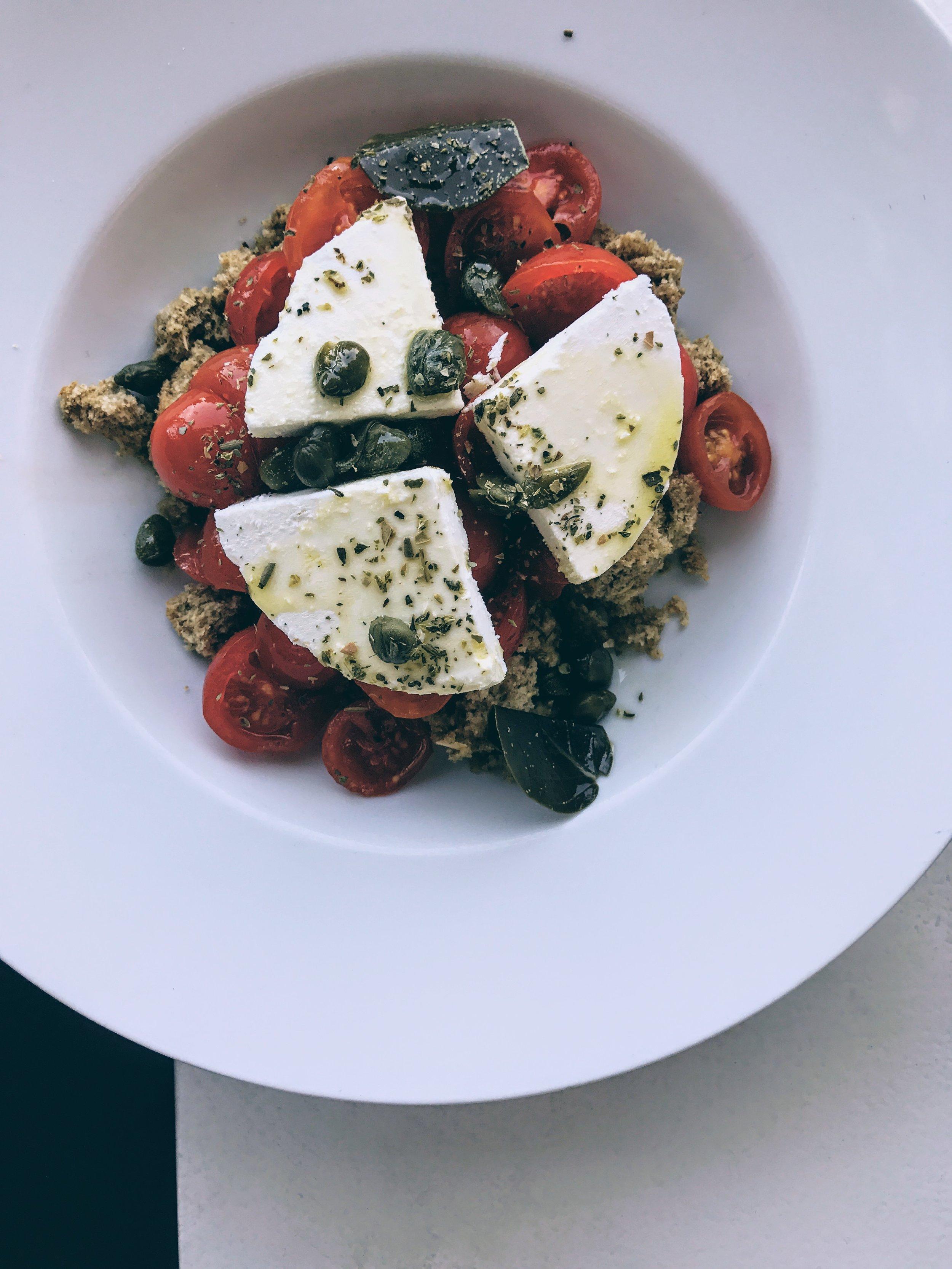 Pomodorini tomato salad with Cretan rusk, caper leaves and Mykonos xinomizithra cheese