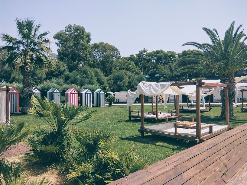 Lounge beds and colored-striped changing rooms at Astir beach