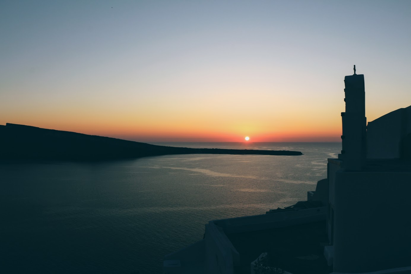The unique sunset of Santorini watched from the hills and cliffs of Oia