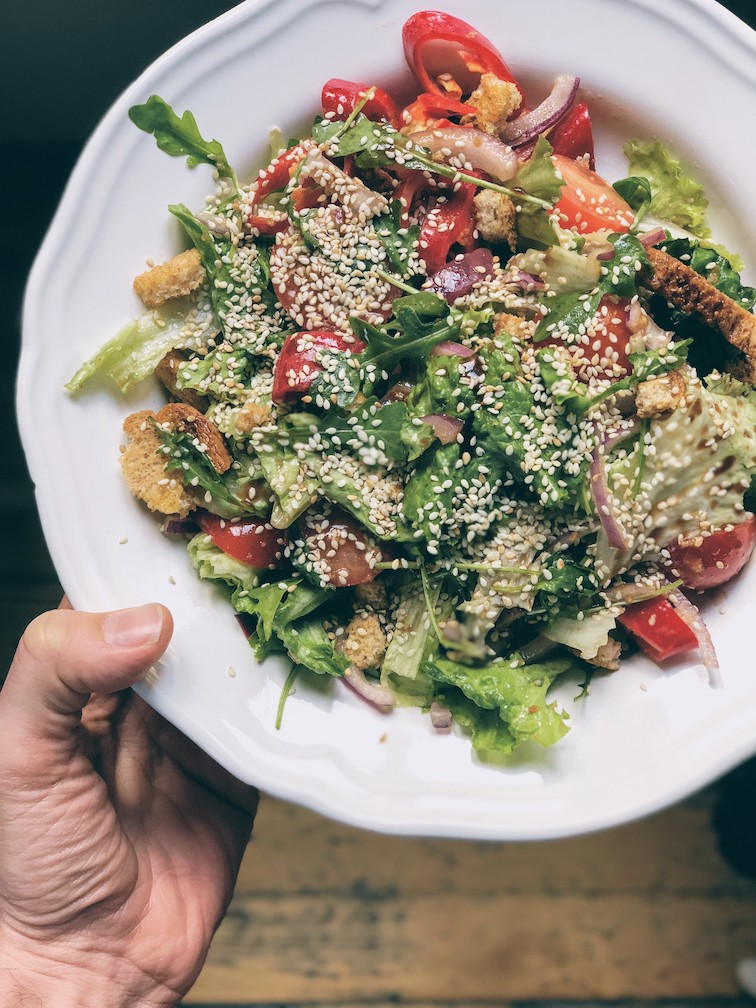 Rocket and lettuce salad with pink tomatoes, peppers and sesame seeds