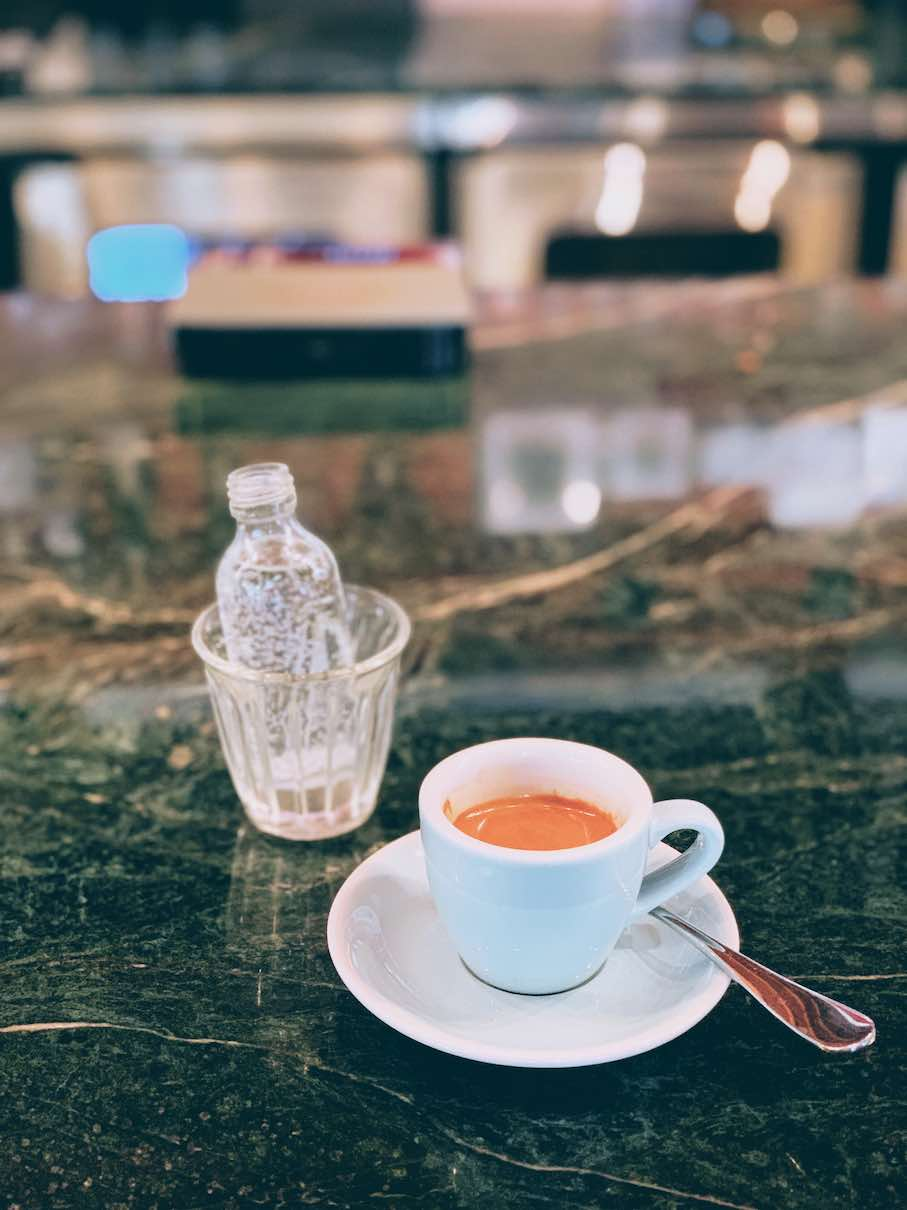 Tasty shot of espresso served with a tiny bottle of sparkling water