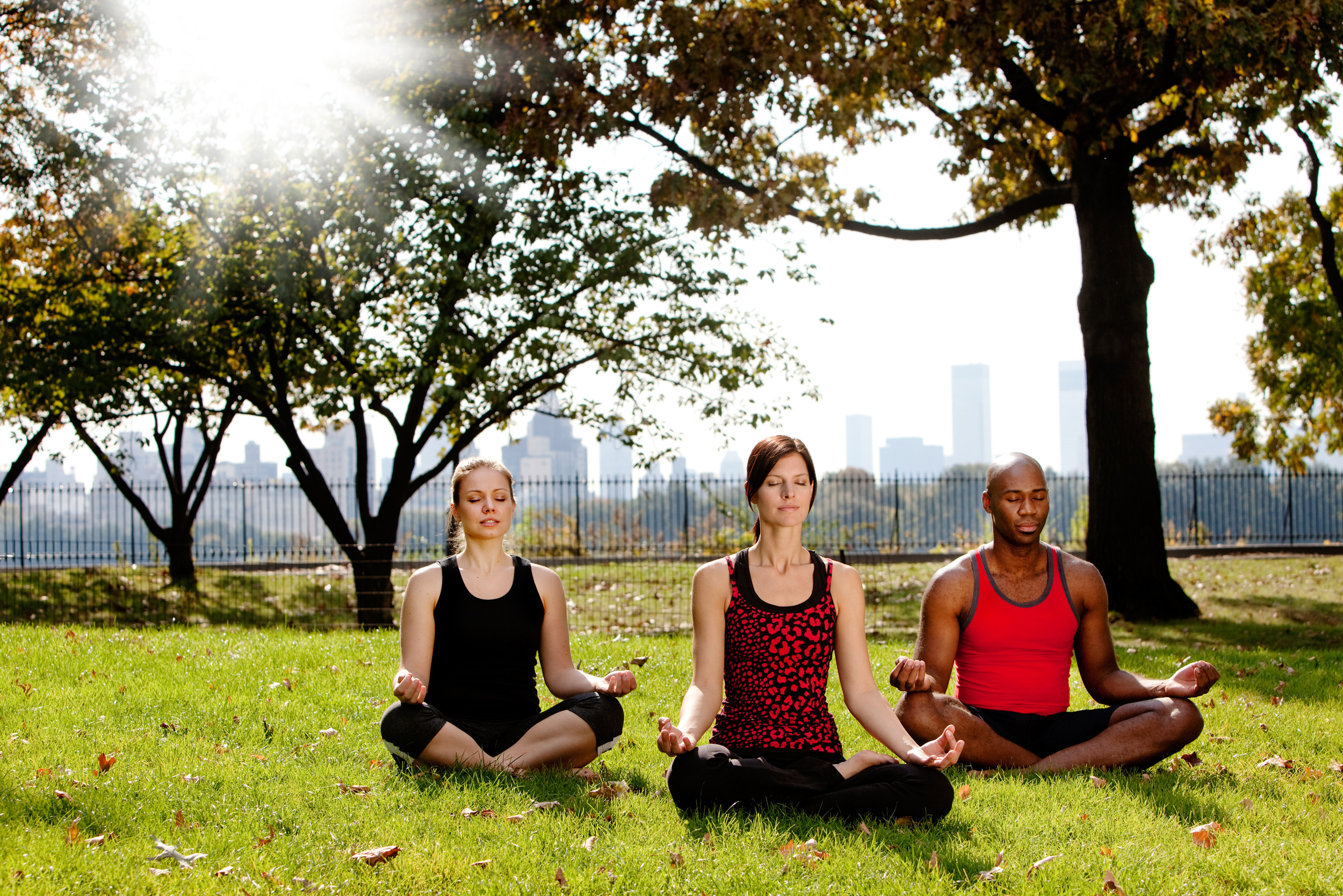 three people meditating in a city park